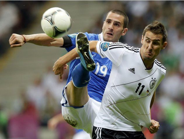 Germany's Klose is challenged by Italy's Bonucci during their Euro 2012 semi-final soccer match at the National stadium in Warsaw