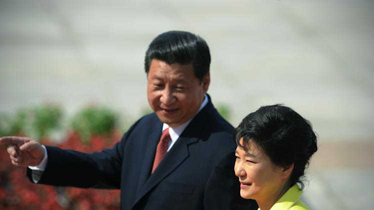 Chinese President Xi Jinping, left, gestures while walking with South Korean President Park Geun-hye, as she inspects a Chinese honor guard during a welcome ceremony outside the Great Hall of the People in Beijing on Thursday, June 27, 2013. The Chinese and South Korean presidents reaffirmed close ties between their nations Thursday at a Beijing summit that brings together North Korea's archrival and its biggest ally, ratcheting up pressure on Pyongyang to rejoin nuclear disarmament talks. (AP Photo/Wang Zhao, Pool)
