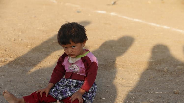 Child from the minority Yazidi sect, who fled violence in the Iraqi town of Sinjar, sits on the ground at Bajed Kadal refugee camp, southwest of Dohuk province