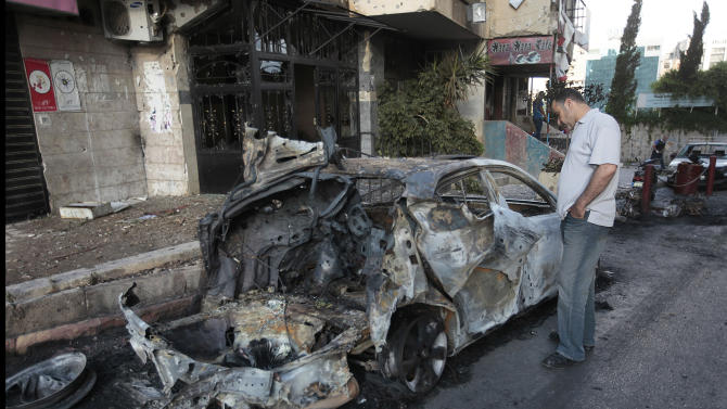 A Lebanese man looks at a burned car that was damaged during clashes between pro- and anti-Syrian Sunni groups in Beirut, Lebanon, Monday, May 21, 2012. Gunmen fired rocket-propelled grenades and machine guns early Monday in intense street battles in the Lebanese capital, wounding and killed several people as fears mounted that the conflict in neighboring Syria was bleeding across the border. The clashes erupted hours after an anti-Syrian cleric and his bodyguard were shot dead in northern Lebanon.(AP Photo/Hussein Malla)