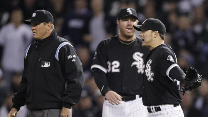 Chicago White Sox's Jake Peavy (44) reacts after being called for a balk against the Tampa Bay Rays during the second inning of a baseball game in Chicago, Thursday, Sept. 27, 2012. At left is first base umpire Chad Fairchild, who did not make the balk call. At center is Adam Dunn. (AP Photo/Nam Y. Huh)