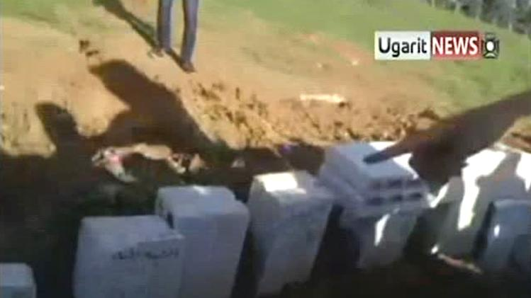 In this image made from amateur video released by Ugarit News and accessed Saturday, May 5, 2012, a resident of the town of Taftanaz, Syria, right, points to what is claimed to be headstones marking a mass grave as he and others explain the scene to a U.N. observer.  The international group Human Rights Watch has said regime soldiers raiding the town on the Turkish border in early April killed 35 detained civilians execution-style and opened fire on others trying to flee. (AP Photo/Ugarit News via AP video) TV OUT, THE ASSOCIATED PRESS CANNOT INDEPENDENTLY VERIFY THE CONTENT, DATE, LOCATION OR AUTHENTICITY OF THIS MATERIAL