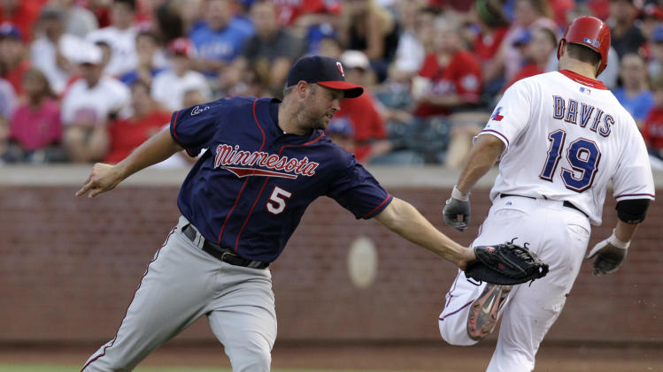 Minnesota Twins right fielder Michael Cuddyer (5) reaches back but is unable to tag out Texas Rangers' Chris Davis (19) on an infield single to short in the third inning of a baseball game, Monday, July 25, 2011, in Arlington, Texas. (AP Photo/Tony Gutierrez)