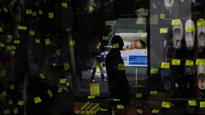 People are reflected in the window of a shoe and handbag store in central Madrid