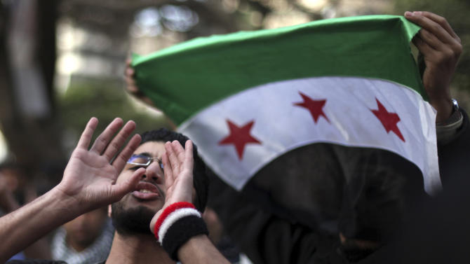 FILE - In this Wednesday, Feb. 6, 2013, file photo, Egyptian and Syrian protesters, with a Syrian revolutionary flag, protest against Iran's President Mahmoud Ahmadinejad during his visit to Egypt for the 12th summit of the Organization of Islamic Cooperation at the Iranian diplomatic representation office in Cairo, Egypt. Once welcomed with open arms in Egypt, Syrians have increasingly found themselves the targets of hate speech and intimidation in the country since the military's ouster of President Mohammed Morsi on July 3, 2013. The backlash stems from the backing Morsi offered to the Syrian opposition during his year in office, as well as the support his Muslim Brotherhood provided to some of the refugees, often in the form of cheap housing and food aid. (AP Photo/Khalil Hamra, File)