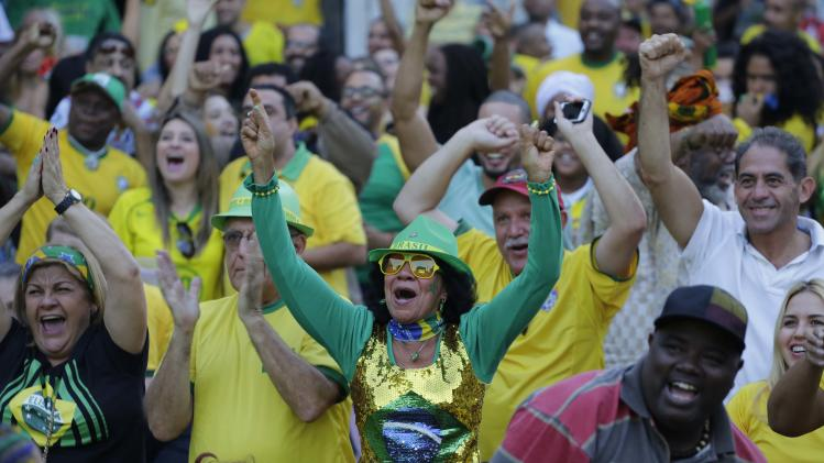 Soccer fans cheer after Brazil scored against Cameroon while watching the match on a big screen in the Bixiga neighborhood, in Sao Paulo, Brazil, Monday, June 23, 2014. Neymar scored twice to give Brazil a 2-1 lead over Cameroon at halftime of their last group A match on Monday. (AP Photo/Nelson Antoine)