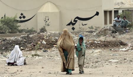 Internally displaced woman walks outside a food distribution centre set up in a sports stadium in Bannu