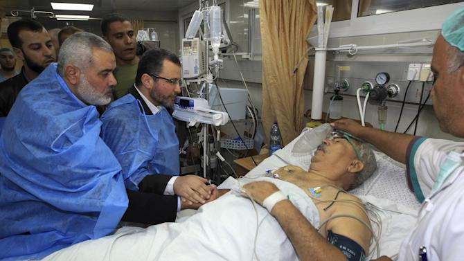 Gaza's Hamas Prime Minister Ismail Haniyeh, left, and Egyptian Prime Minister Hesham Kandil, second left, visit a man wounded in an Israeli strike, at the hospital in Gaza City, Friday, Nov. 16, 2012.  Early Friday, 85 missiles exploded within 45 minutes in Gaza City, sending black pillars of smoke towering above the coastal strip's largest city. The military said it was targeting underground rocket-launching sites. The Israeli offensive has not deterred the militants from firing more than 400 rockets aimed at southern Israel since Wednesday, the military said.(AP Photo/Mahmud Hams, Pool)