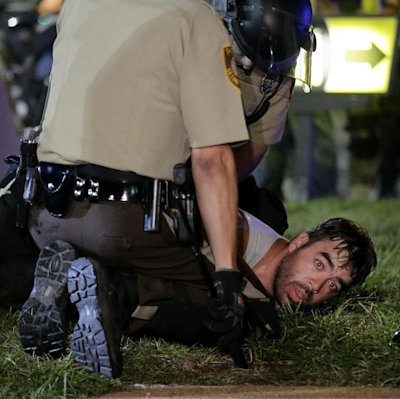 A man is detained by police during a protest Monday, Aug. 18, 2014, for Michael Brown, who was killed by a police officer Aug. 9 in Ferguson, Mo. Brow...