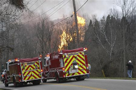 Fire crews look on as flames burn from a gas line explosion near Sissonville, West Virginia December 11, 2012. The explosion in Sissonville, about 10 miles north of Charleston, setting several houses and buildings on fire, authorities said. REUTERS/The Charleston Gazette/Rusty Marks