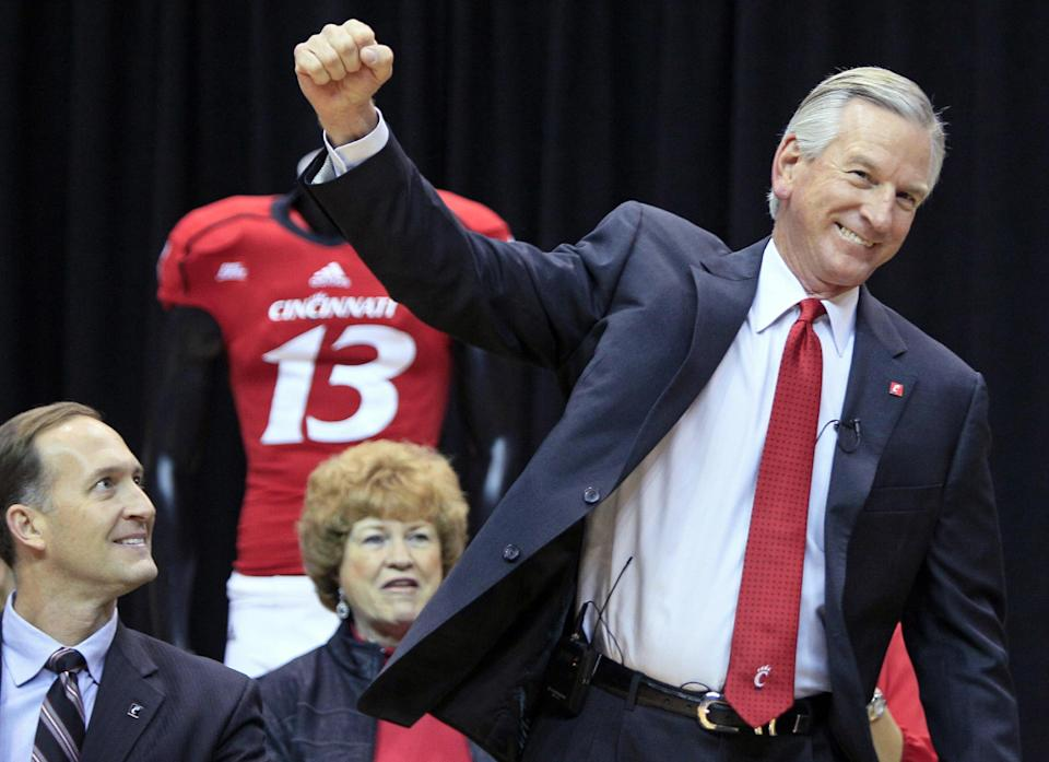 Tommy Tuberville pumps his fist as he is introduced as the new head football coach at the University of Cincinnati, Saturday, Dec. 8, 2012, in Cincinnati. Cincinnati athletic director Whit Babcock, left, watches. Tuberville had been head coach at Texas Tech, and previously at Auburn and Mississippi. (AP Photo/Al Behrman)