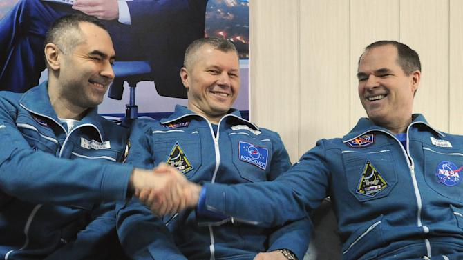 Russian cosmonauts Yevgeny Tarelkin, left, Oleg Novitsky, center, and NASA's astronaut Kevin Ford have light moments as they pose for a photo at the airport of the Kazakh city of Kostanai after their landing in northern Kazakhstan, Saturday, March 16, 2013. A Soyuz space capsule carrying a Russian-American crew landed Saturday morning on the steppes of Kazakhstan, safely returning the three men to Earth after a 144-day mission to the International Space Station. The crew members had been scheduled to return on Friday, but the landing was postponed by a day because of bad weather. (AP Photo/Alexander Nemenov, Pool)