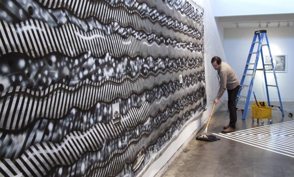 In this Tuesday, Feb. 19, 2013 photo, Ryan Travis Christian mops the floor in front of his wall-sized charcoal drawing at the Contemporary Art Museum in Raleigh, N.C. The Chicago artist completely reworked his drawing several days into his first museum exhibition. (AP Photo/Allen Breed)