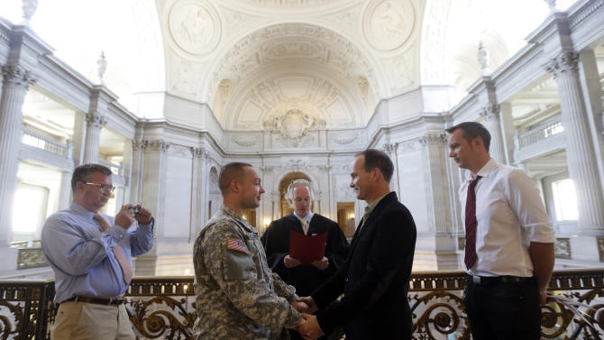 Army Capt. Michael Potoczniak, center left, and Todd Saunders, of El Cerrito, Calif., are married by deputy marriage commissioner John Loschmann, center, as witnesses Bill Hershon, left, and Sean Boileau watch at City Hall in San Francisco, Saturday, June 29, 2013. Dozens of gay couples waited excitedly Saturday outside of San Francisco's City Hall as clerks resumed issuing same-sex marriage licenses, one day after a federal appeals court cleared the way for the state of California to immediately lift a 4 ½ year freeze. Big crowds were expected from across the state as long lines had already stretched down the lobby shortly after 9 a.m. City officials decided to hold weekend hours and let couples tie the knot as San Francisco is also celebrating its annual Pride weekend expected to draw as many as 1 million people. (AP Photo/Marcio Jose Sanchez)
