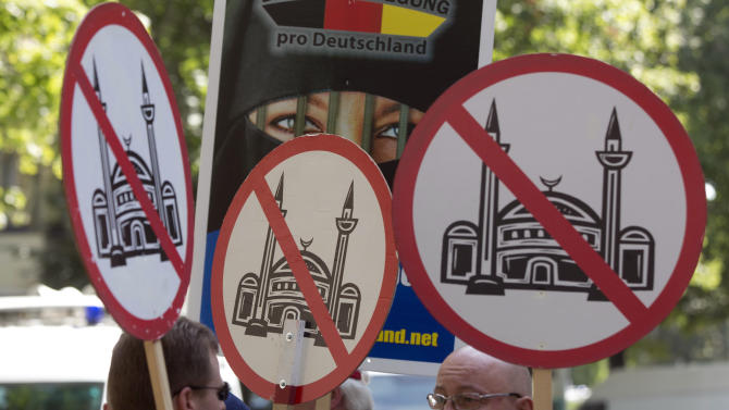 """Demonstrators display signs, during a protest in front of a mosque in Berlin, Germany, Saturday, Aug. 18, 2012. A Berlin court had allowed the demonstration of the far-right group ' Pro Deutschland'  held under the slogan """"Islam does not belong in Germany — stop Islamization.""""  (AP Photo/Gero Breloer)"""