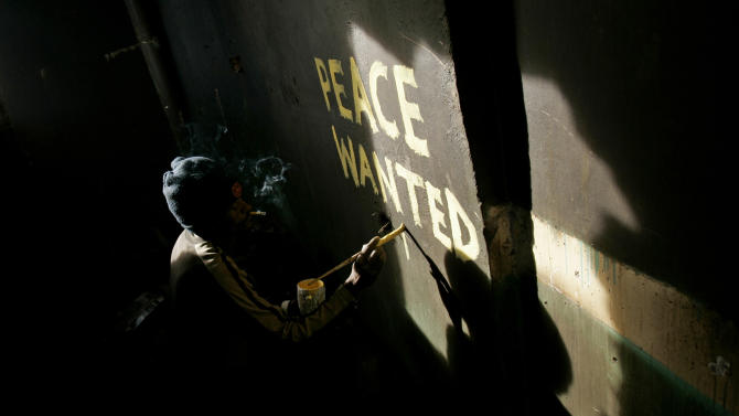 FILE - In this Tuesday, Feb. 19, 2008 file photo, Solomon Muyundo, a Kenyan artist who uses the tag Solo7, paints a peace slogan in a damaged house following post-election violence in the Kibera slum of Nairobi, Kenya. Kenya's first nation-wide vote since devastating violence broke out after the nation's 2007 presidential election will be closely monitored by the international community and local observers to help ward off potential problems, officials said Monday, Jan. 28th, 2013. (AP Photo/Bernat Armangue, File)
