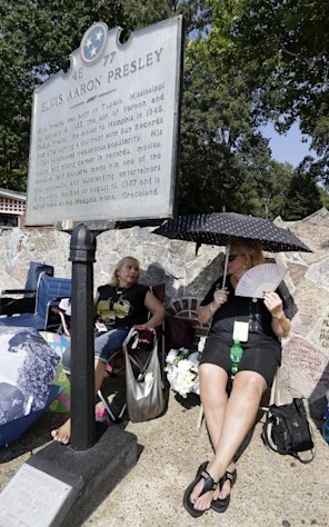 Elvis Presley fans Cheryl Skogen, left, and Susan Struss, both from Los Angeles, wait in line outside Graceland, Presley&#39;s Memphis, Tenn. home, on Wednesday, Aug. 15, 2012. Fans are lined up to take part in the annual candlelight vigil marking the 35th anniversary of Presley&#39;s death. (AP Photo/Mark Humphrey)