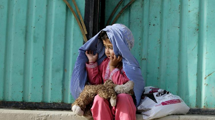An Afghan girl adjusts her burqa in Kabul, Afghanistan, Thursday, Aug. 16, 2012. (AP Photo/Ahmad Jamshid)