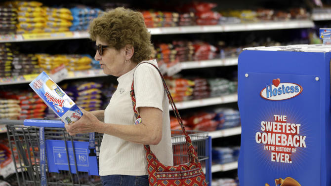 FILE-- In this Friday, July 12, 2013, file photo Jo Mullen picks up a box of Twinkies at Wal-Mart, in Bristol, Pa. The new owners of Hostess have leaner operating costs now that they're no longer using unionized workers. It turns out the spongy yellow cakes may also be a little smaller than the last Twinkies people remember eating. (AP Photo/Matt Rourke)