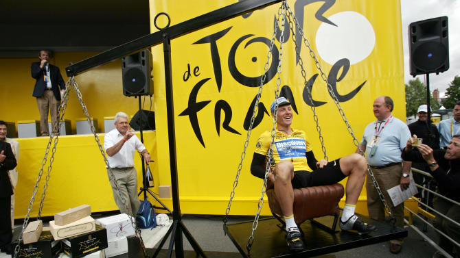 FILE - In this July 7, 2005, file photo, Lance Armstrong laughs as he has his weight matched with boxes containing champagne bottles while seated on a scale before the sixth stage of the Tour de France cycling race between Troyes and Nancy, eastern France. In 2012 Armstrong was stripped of his Tour de France titles, lost most of his endorsements and was forced to leave the Livestrong foundation last year after the U.S. Anti-Doping Agency issued a damning, 1,000-page report that accused him of masterminding a long-running doping scheme. (AP Photo/Christophe Ena, File)