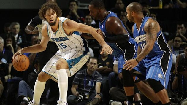 New Orleans Hornets center Robin Lopez (L) controls the ball over Orlando Magic centers Glen Davis (2nd R) and guard Jameer Nelson (R) during their exhibition NBA game in Mexico City (Reuters)