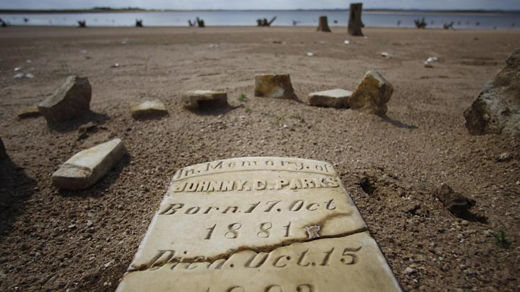 In this Oct. 5, 2011 photo, a child's grave site, normally at least 20 to 30 feet underwater, has joined other remnants of old Bluffton, Texas, resurfacing on the now dry, sandy lake near Bluffton, as the Texas drought shrinks the state's largest inland lake.  (AP Photo/Eric Gay)