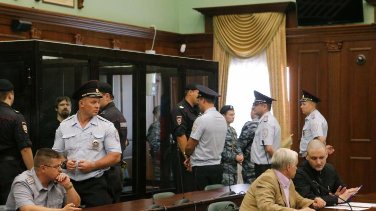 Opposition leaders Udaltsov and Razvozhayev attend a court hearing in Moscow