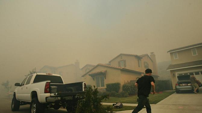 A resident rushes to help evacuate a home as a brush fire burning in Day Creek near the Etiwanda Preserve in Rancho Cucamonga, Calif., nears their neighborhood on Wednesday, April 30, 2014. Fire officials say winds gusting to 60 mph are pushing the flames through the foothills of the San Bernardino Mountains east of Los Angeles, although no homes are in immediate danger. Several neighborhoods and at least seven schools in Rancho Cucamonga have been evacuated. There's no word on what sparked the blaze but it comes in the midst of a heat wave that's created extreme fire danger. (AP Photo/The Press-Enterprise, Stan Lim) MAGS OUT; MANDATORY CREDIT