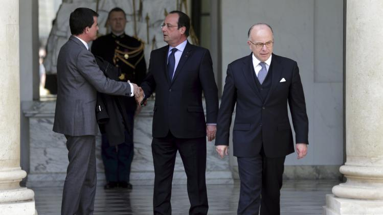 French President Hollande speaks with Prime Minister Valls near Interior Minister Cazeneuve following the weekly cabinet meeting at the Elysee Palace in Paris
