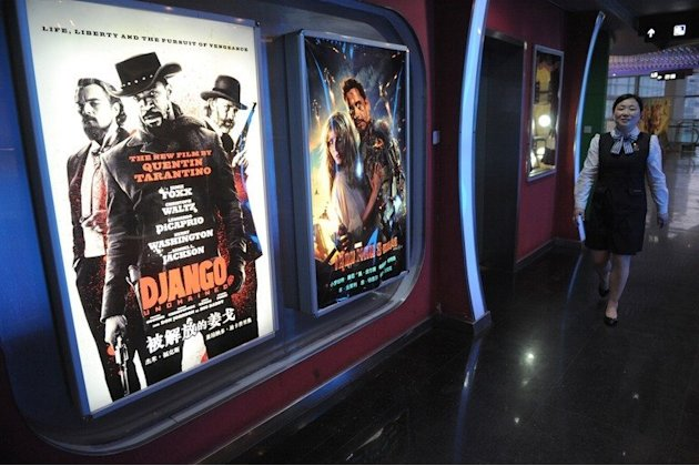 "A woman walks past a movie poster for Quentin Tarantino's ""Django Unchained"" at a theatre in Shanghai on May 12, 2013"