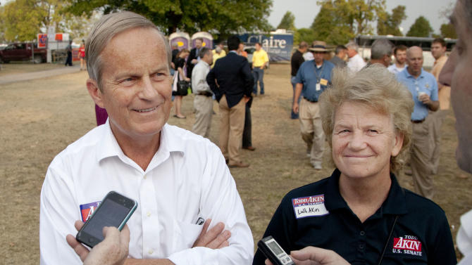"In this Thursday, Aug. 16, 2012 photograph, Rep. Todd Akin, R-Mo., and his wife Lulli, talk with reporters while attending the Governor's Ham Breakfast at the Missouri State Fair in Sedalia, Mo. Akin was keeping a low profile, Monday, Aug. 20, 2012, a day after a TV interview in which he said that women's bodies can prevent pregnancies in ""a legitimate rape"" and that conception is rare in such cases. (AP Photo/Orlin Wagner)"