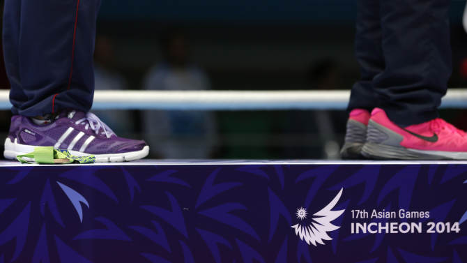 The bronze medal rejected by India's L. Sarita Devi lies on the podium beside the feet of athletes during the medal ceremony for the women's light 60-kilogram division boxing at the 17th Asian Games in Incheon, South Korea, Wednesday, Oct. 1, 2014.  India's protest against the outcome of an Asian Games boxing semifinal that was awarded to South Korea's Park Ji-na over Devi in the women's 60-kilogram division was rejected on Tuesday. Devi rejected her medal in protest against the result. (AP Photo/Kin Cheung)