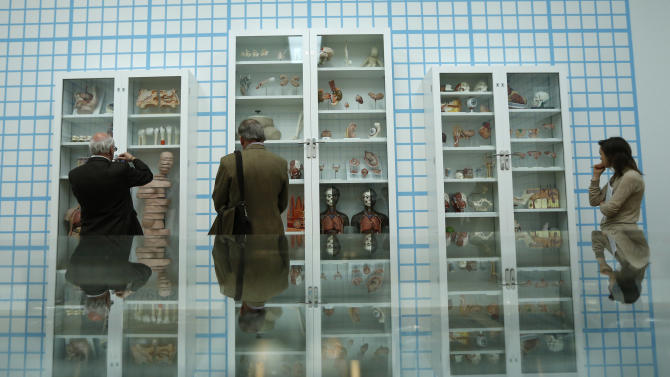 """People are reflected as they look at British artist Damien Hirst's year 2000 piece """"Trinity - Pharmacology, Physiology, Pathology"""", consisting of glass, faced particle board, wood, steel and anatomical models, during a media preview of the first substantial show of his work in the UK at the Tate Modern gallery in London, Monday, April 2, 2012.  The exhibition, timed for the culmination of the Cultural Olympiad and due to open to the public on Wednesday, showcases over 70 of Hirst's works since he first came to public attention in 1988.  (AP Photo/Matt Dunham)"""