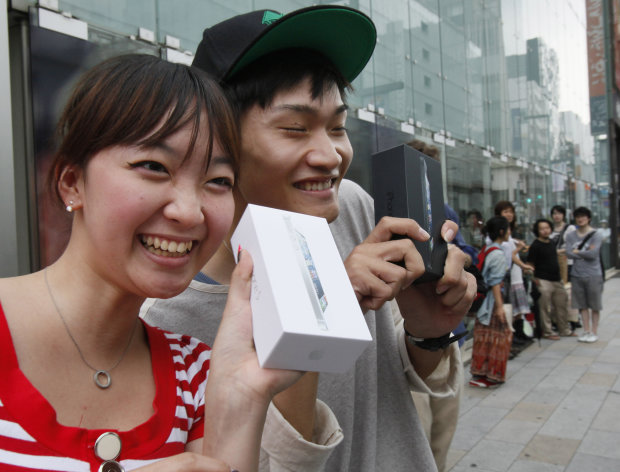 Kae Shibata 20, left, and Yutaro Noji, 21, show off Apple&#39;s iPhone 5 after they bought at a store in Tokyo Friday morning, Sept. 21, 2012. (AP Photo/Koji Sasahara)