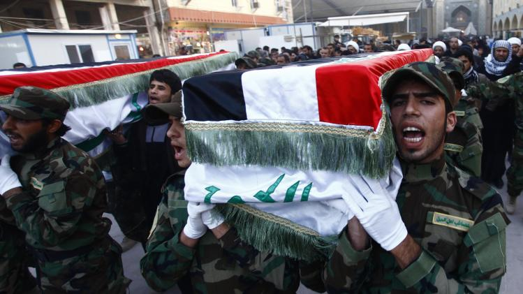 Members of Shi'ite group Asaib Ahl al-Haq, who support Syrian President Bashar al-Assad, carry the coffins of fighters from their group, during a funeral in Najaf