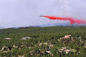 An aircraft releases a fire-retardant solution to help stop the spreading of the burning fires at Black Forest, Colorado
