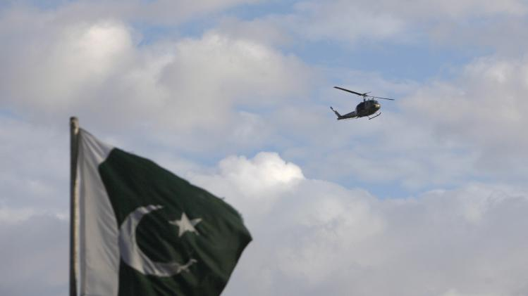 A helicopter flies past a Pakistan's national flag in the premises of parliament house during the Revolution March in Islamabad
