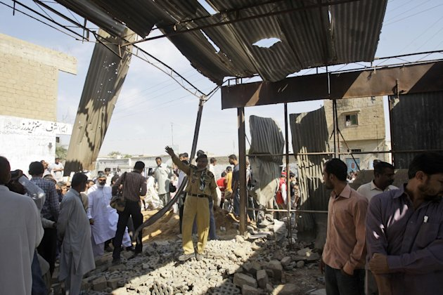 Pakistanis gather at the site of a bomb blast, in Karachi, Pakistan, Monday, Nov. 26, 2012. A bomb hidden in a cement construction block exploded in the southern city of Karachi killing at least one p