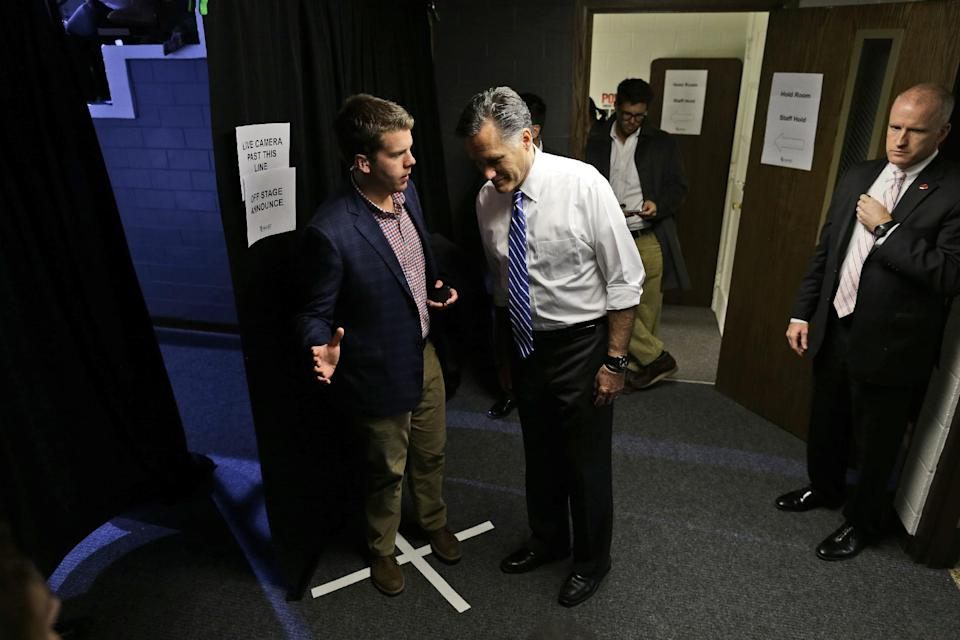 Republican presidential candidate and former Massachusetts Gov. Mitt Romney is briefed by his aide Garrett Jackson backstage as he is introduced by his vice presidential running mate Rep. Paul Ryan, R-Wis., at the Celina Fieldhouse in Celina, Ohio, during a campaign rally, Sunday, Oct. 28, 2012. (AP Photo/Charles Dharapak)