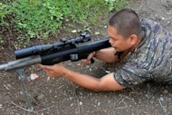 Guiazakallaha Jaafar aims his 50 caliber sniper rifle inside the Camp of the Moro Islamic Liberation Front (MILF) in Sultan Kudarat southern Philippines on October 10. Jaafar, 28, who boasts of 3,000 fighters under his command, said he and his men believed their leaders would not order them disarmed without without consensus from key officers