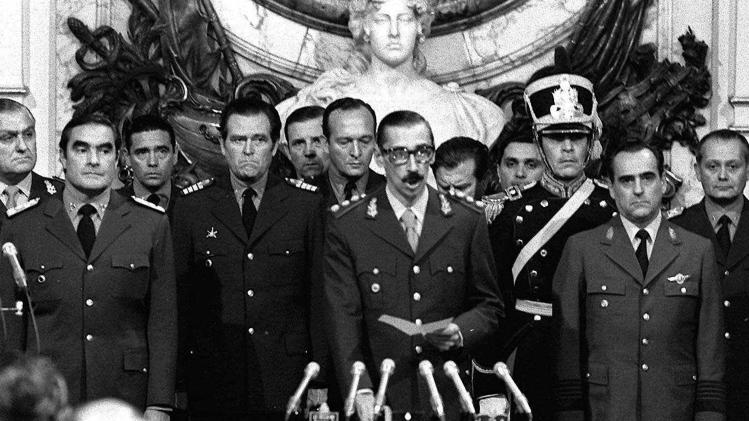 """FILE - In this March 24, 1976 file photo, Gen. Jorge Rafael Videla, center, is sworn-in as president at the Buenos Aires Government House accompanied by Adm. Emilio Massera, second from left, and Brig. Orlando Agosti, second from right, members of the junta that overthrew President Isabel Peron. The former Argentine dictator died of natural causes Friday, May 17, 2013, while serving life sentences at the Marcos Paz prison for crimes against humanity. Videla took power in a 1976 coup and led a military junta that killed thousands of his fellow citizens in a dirty war to eliminate """"subversives."""" He was 87. (AP Photo/Eduardo Di Baia, File)"""