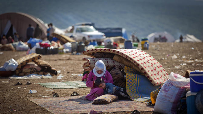 A Syrian family who fled from the violence in their village, sit next to their belongings at a displaced camp, in the Syrian village of Atma, near the Turkish border with Syria. Wednesday, Nov. 7, 2012. (AP Photo/ Khalil Hamra)