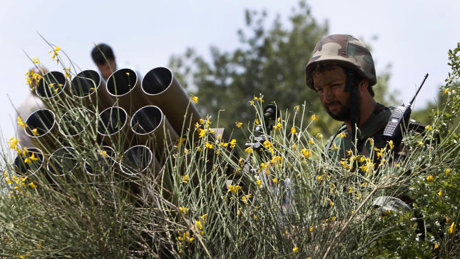 In this picture taken on May 22, 2010, a Hezbollah fighter stands behind an empty rocket launcher while explaining to the group various tactics and weapons used against Israeli soldiers on the battlefield, during a trip to Hezbollah strongholds, in Sojod village, southern Lebanon. Lebanon's prime minister has expressed his readiness to cooperate with Bulgarian authorities over a bomb attack linked to Hezbollah that killed five Israelis and their Bulgarian driver, in a statement Tuesday, Feb. 5, 2013. Prime Minister Najib Mikati whose Cabinet is dominated by members of the Shiite Muslim group and its allies also says he condemns and rejects any attack that targets an Arab or foreign country.(AP Photo/Hussein Malla)
