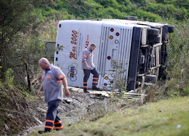Workers check out a bus which overturned coming off at an exit ramp on Route 80 in Wayne, N.J. Saturday, Oct. 6, 2012. The chartered tour bus from Toronto carrying about 60 people overturned on an interstate exit ramp. Three people have been taken to hospital with non-life-threatening injuries. (AP Photo/Bill Kostroun)