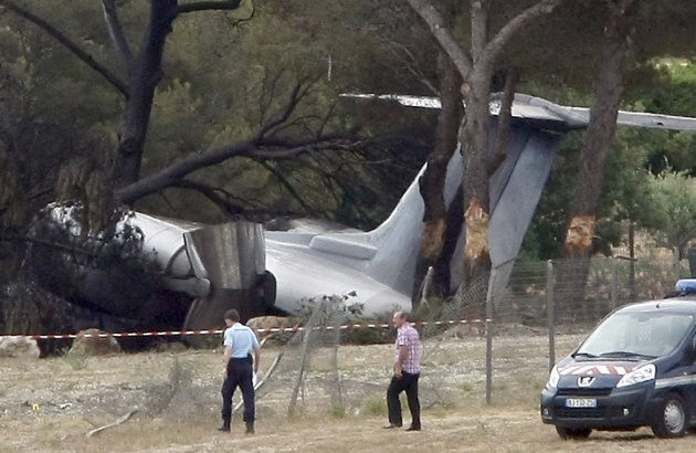 Police Officers walk near the plane that crashed on landing at Le Castellet airport, near Toulon, southern France, Friday, July 13, 2012. Three US citizen died in the accident. (AP Photo/Claude Paris)