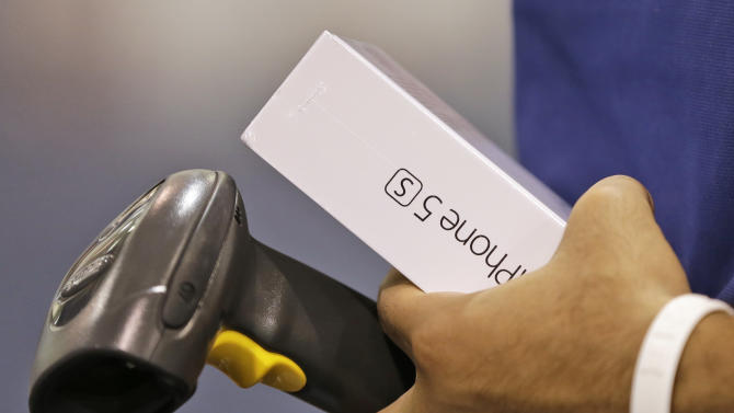 FILE - In this Friday, Sept. 20, 2013, file photo, a Best Buy employee prepares to scan a new iPhone 5S during the opening day of sales of the new phone in Richmond, Va. (AP Photo/Steve Helber, File)