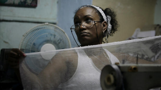 """In this Tuesday Aug. 2, 2011 photo, seamstress Anisia Cardenas works on her sewing machine in Havana. She had set up a stall in a neighbor's patio that she rented for 50 pesos ($2) a day. Unable to meet costs, she says she gave up on the stall in March and now works out of her kitchen in the working-class El Cerro neighborhood. Cardenas says she has noticed a huge dip in business in the past few months, which she attributes to rising competition. Also, she said, raw materials are costly, forcing her to charge prices customers can't afford. """"I'm going to give it two more months, but I am thinking of turning in the license,"""" she said. """"It will be a very sad day if I do."""" (AP Photo/Javier Galeano)"""