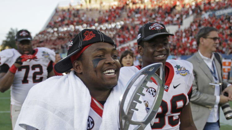 Georgia fullback Alexander Ogletree carries the trophy off the field after Georgia defeated Nebraska 45-31 in the Capital One Bowl NCAA football game, Tuesday, Jan. 1, 2013, in Orlando, Fla. (AP Photo/John Raoux)