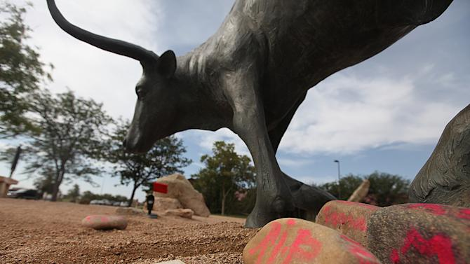 Memorials rest at the feet of a longhorn statue at the National Ranching Heritage Center in Lubbock, Texas, Tuesday, June 25, 2013 where 14-year-old Miguel Martinez died as the result of an accident. Martinez ran into the bull statue while playing hide-and-seek with friends and was impaled on the horn of the statue early Saturday morning, June 22, 2013. (AP Photo/Lubbock Avalanche-Journal,Zach Long)