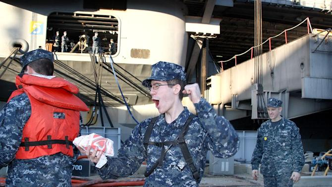 IMAGE DISTRIBUTED FOR TACO BELL - After being deployed in the Middle East for six months, a sailor reacts to being handed Doritos Locos Tacos during the return of the USS Eisenhower Carrier Strike Group at the Naval Station in Norfolk, Va., on Wednesday, Dec. 19, 2012. In gratitude for their service, Taco Bell provided the sailors and their families with their first meal after returning from six months of operations in the Middle East. (Lisa Billings/AP Images for Taco Bell)